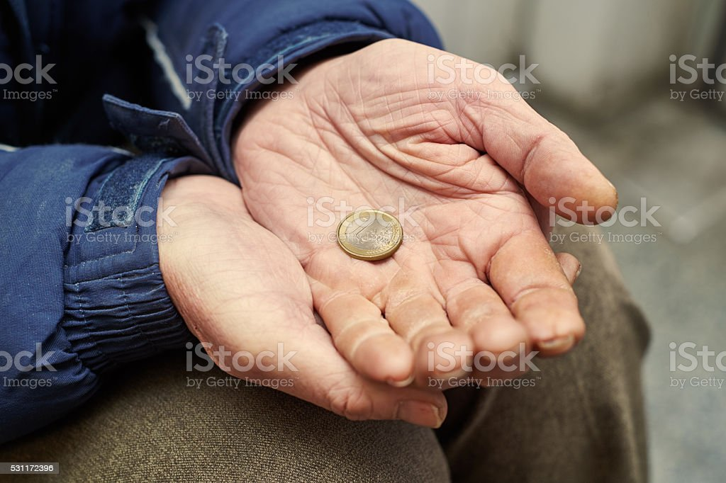 hands of beggar with one euro coin begging for money stock photo