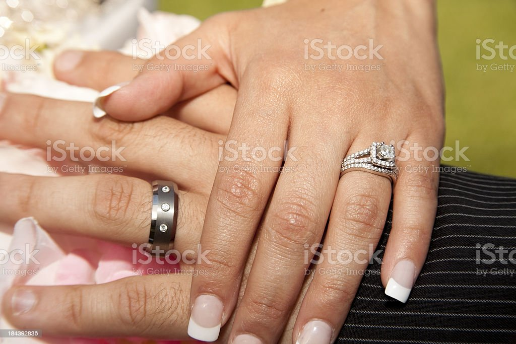 Hands of Bride and Groom with wedding rings plus bouquet stock photo