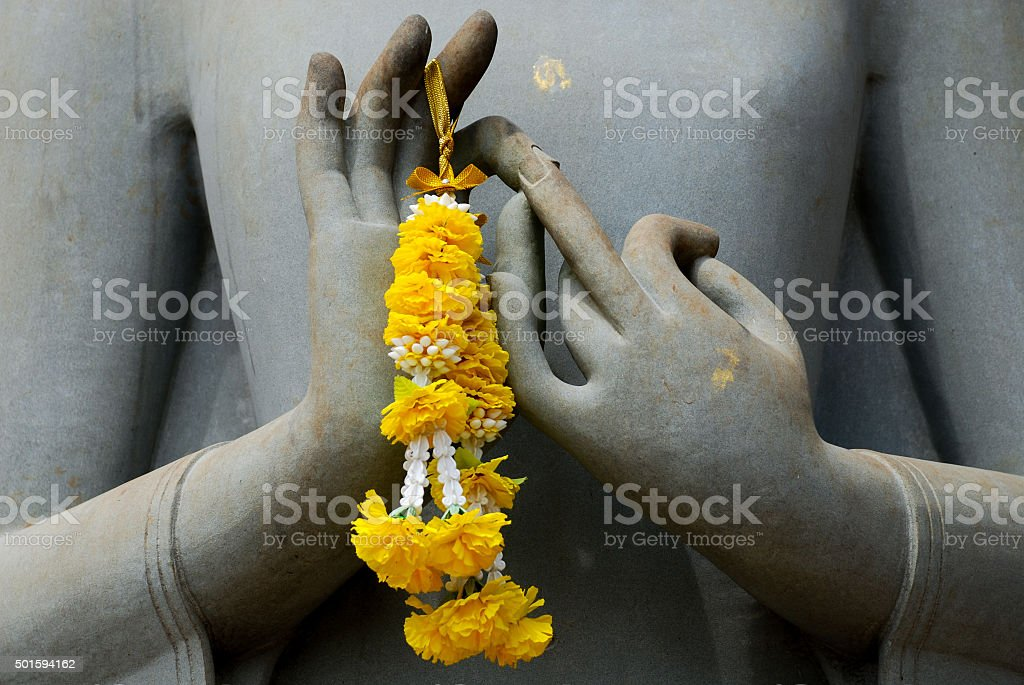 Hands of Budhha statue with flower garland stock photo