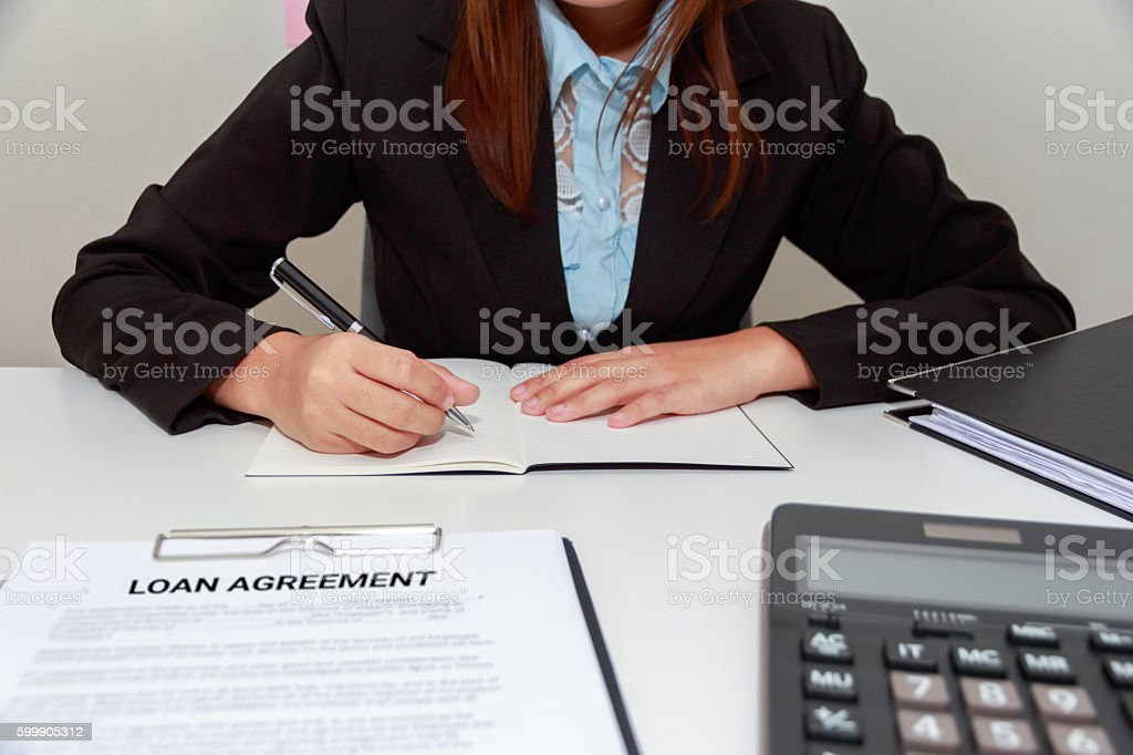 Hands of business woman writing on notebook with loan agreement stock photo