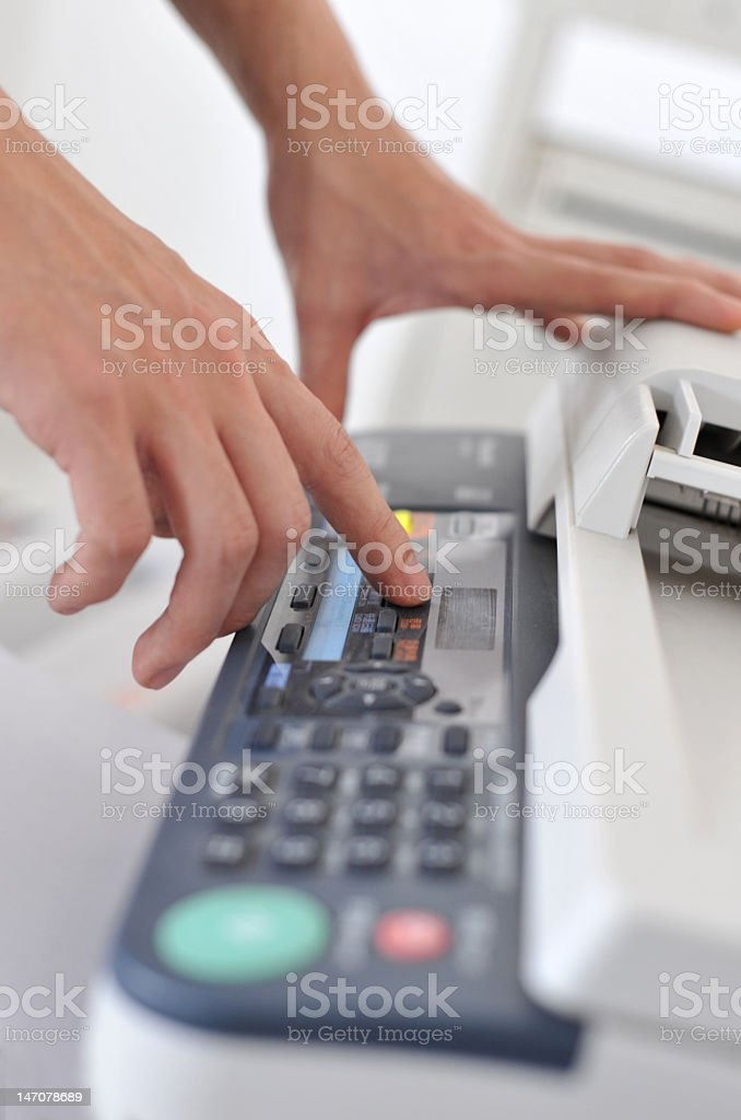 Hands of businessperson operating a fax machine stock photo