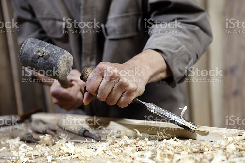 hands of carpenter with hammer and chisel in carpentry stock photo