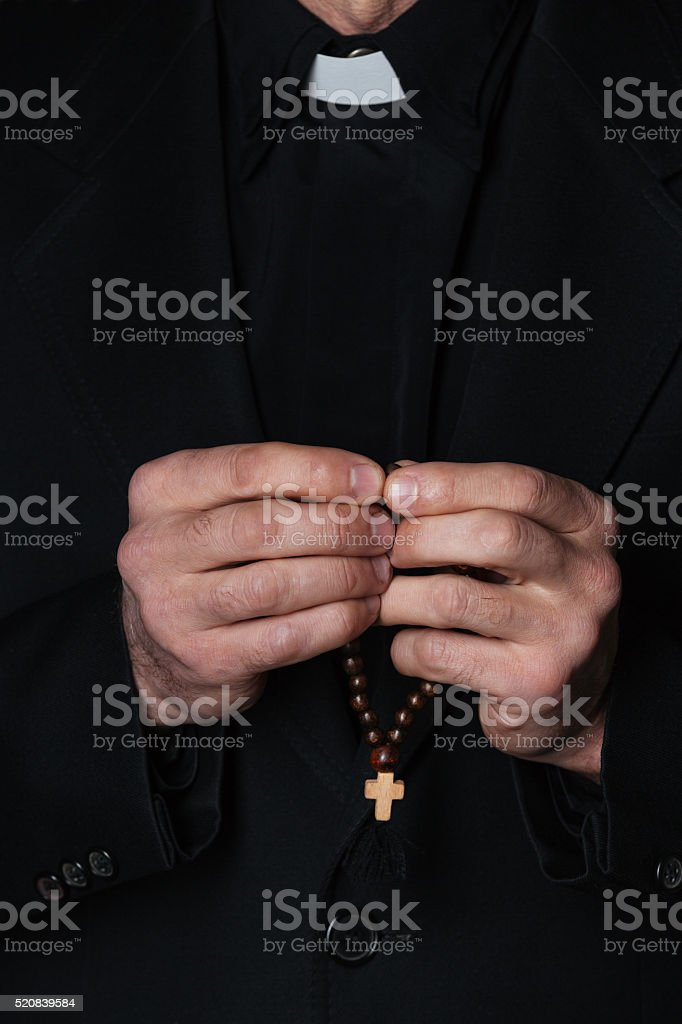 Hands of catholic priest holding rosary stock photo