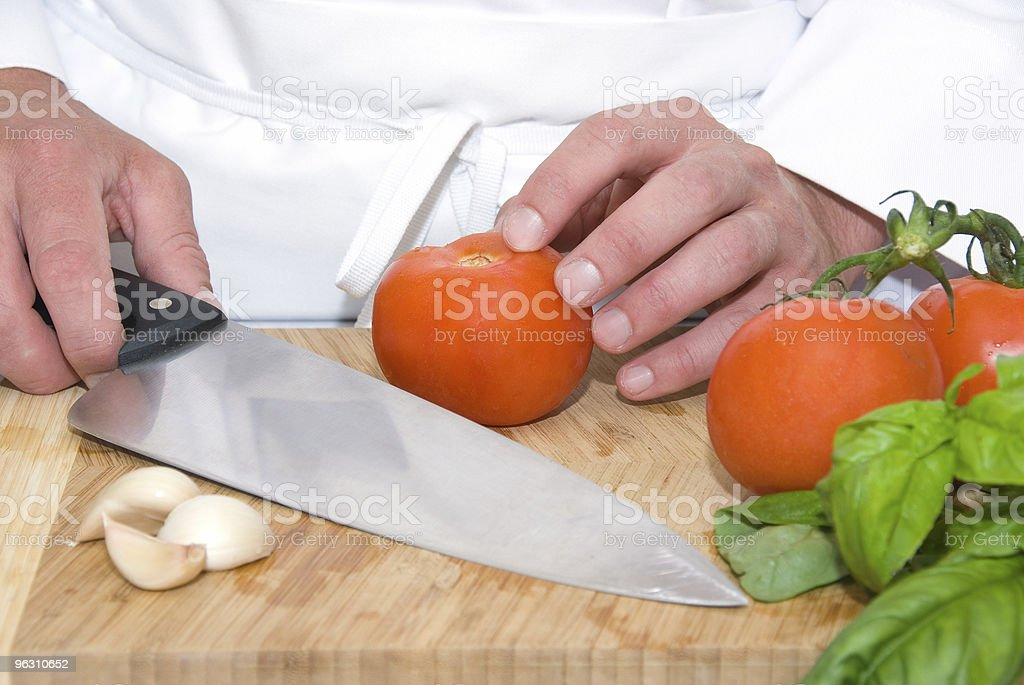 Hands of chef cutting a tomato stock photo