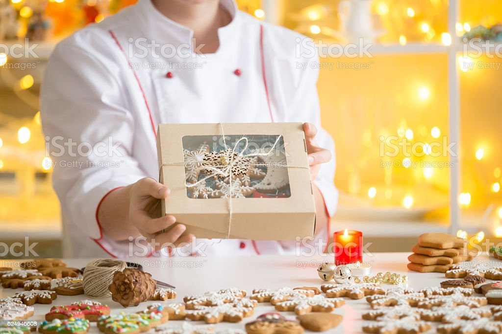 Hands of confectioner showing a box with gingerbread cookies stock photo