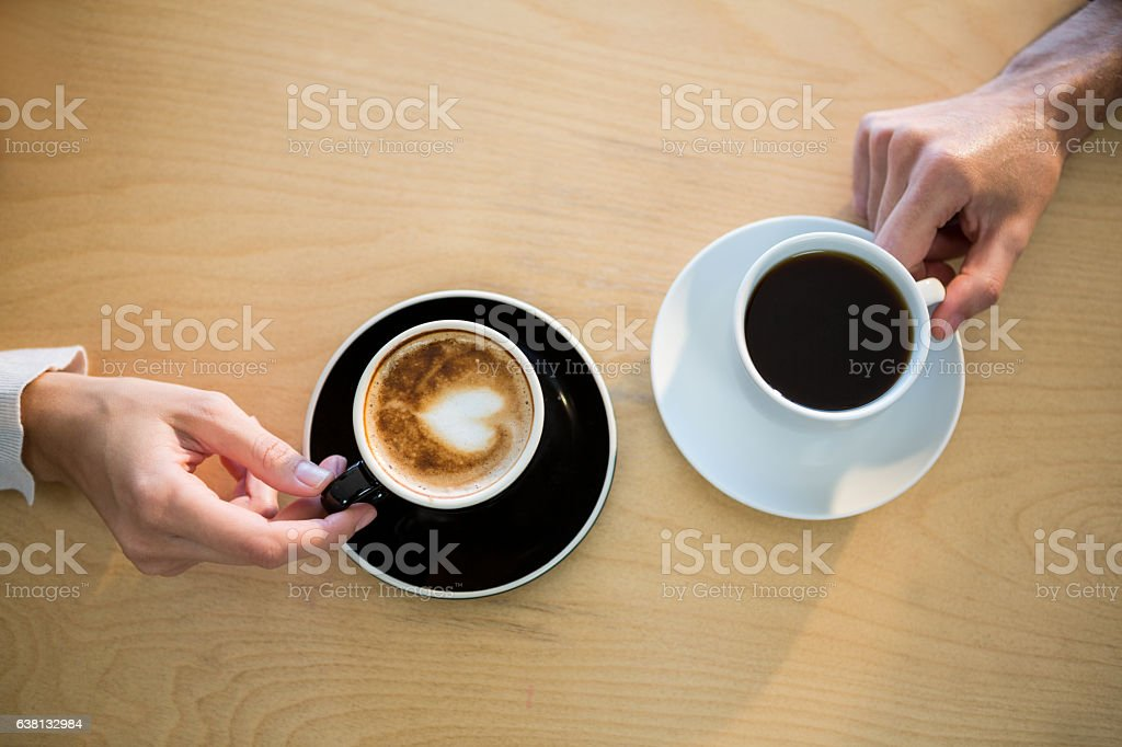 Hands of couple holding cup of coffee stock photo