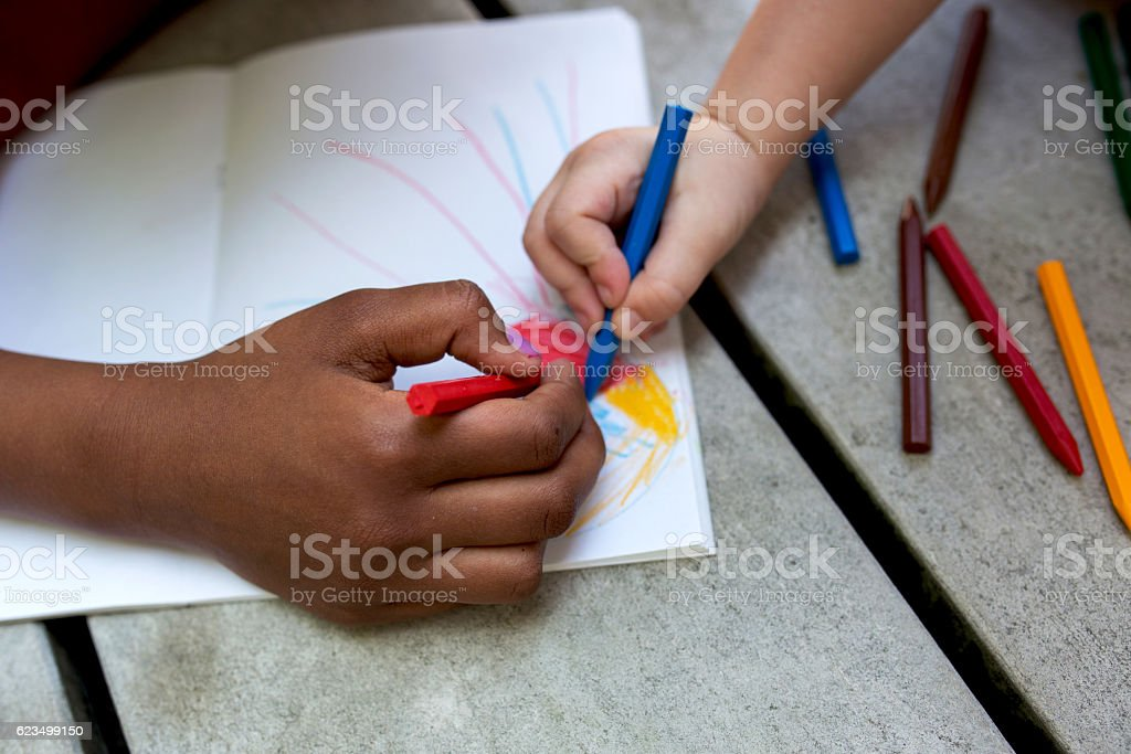 Hands of creative children drawing on paper. stock photo