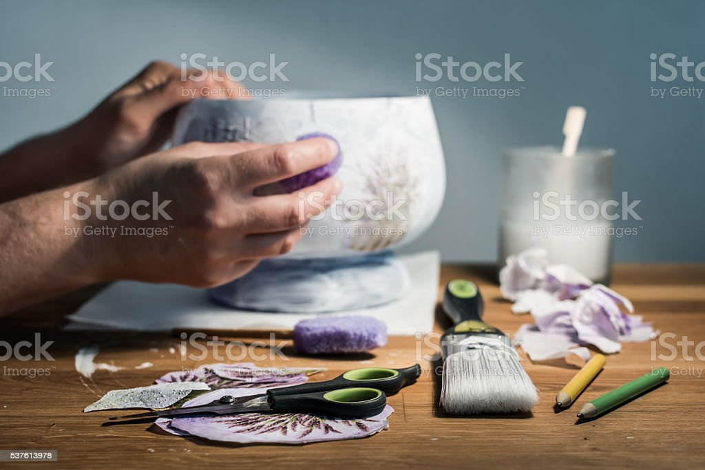 Hands of decoupage artist and artistic supplies on the table. stock photo