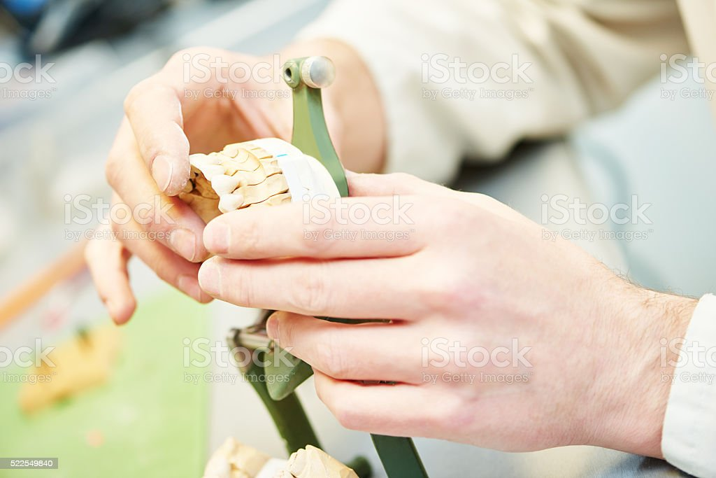 hands of dental technician working with tooth dentures stock photo