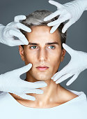 Hands of doctors in medical gloves touching face