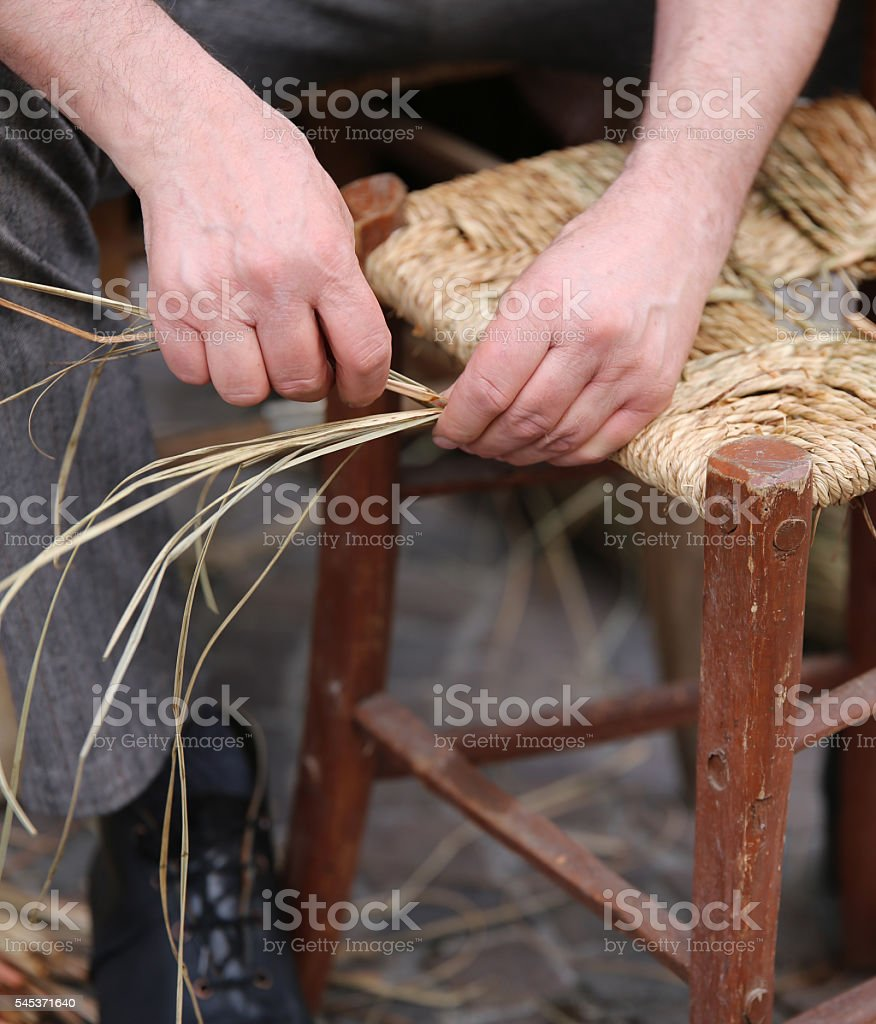 hands of elder repairer of chairs along the street stock photo