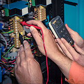 Hands of electricians with multimeter probe at electrical switchgear cabinet