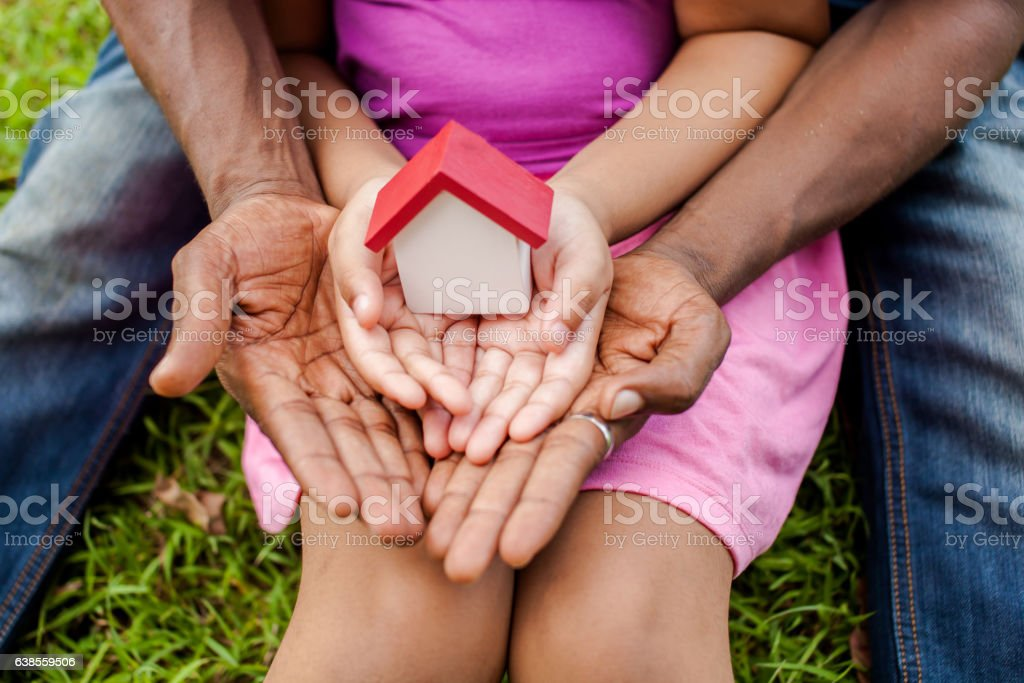 Hands of family together holding house in green park stock photo