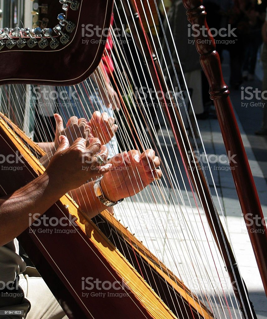 Hands of father and son playing the harp in Stockholm stock photo