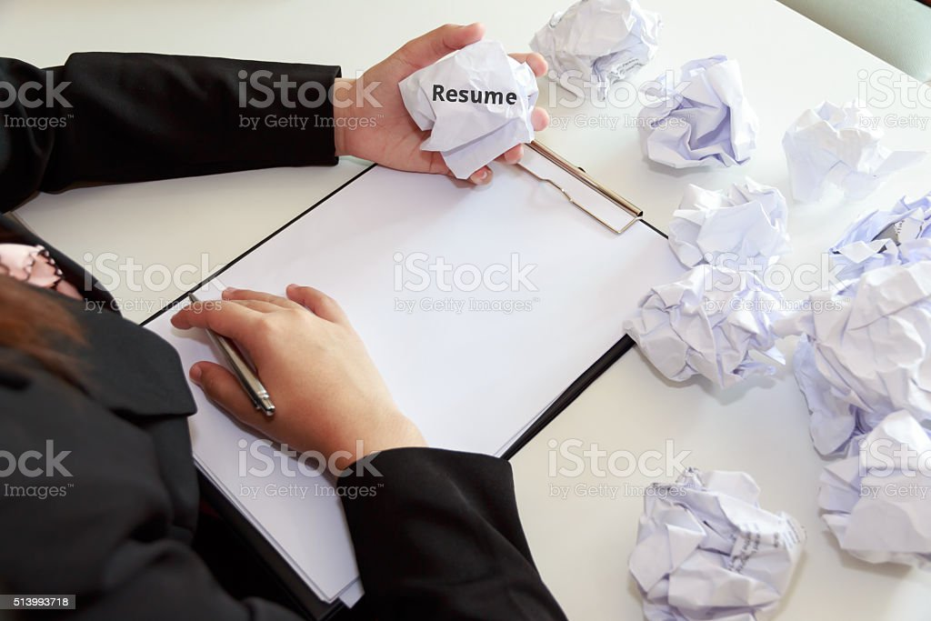Hands of female crumple sheets of Resume at the desk stock photo