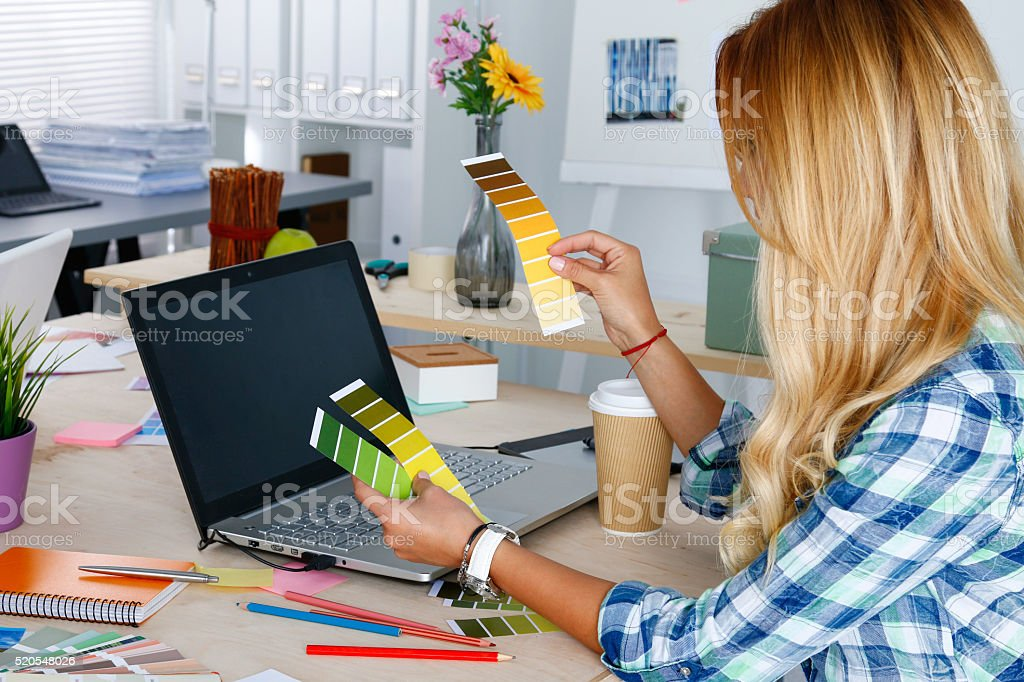 Hands of female designer in office working with colour samples stock photo