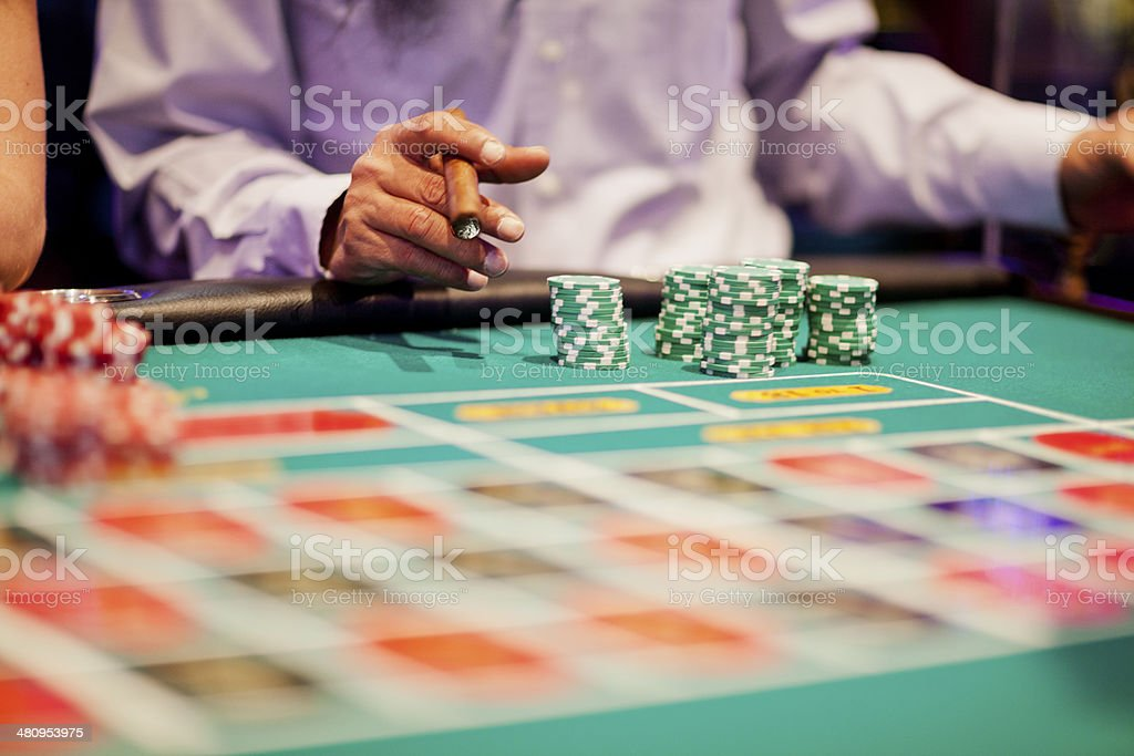 Hands of gamblers making bets at roulette table stock photo