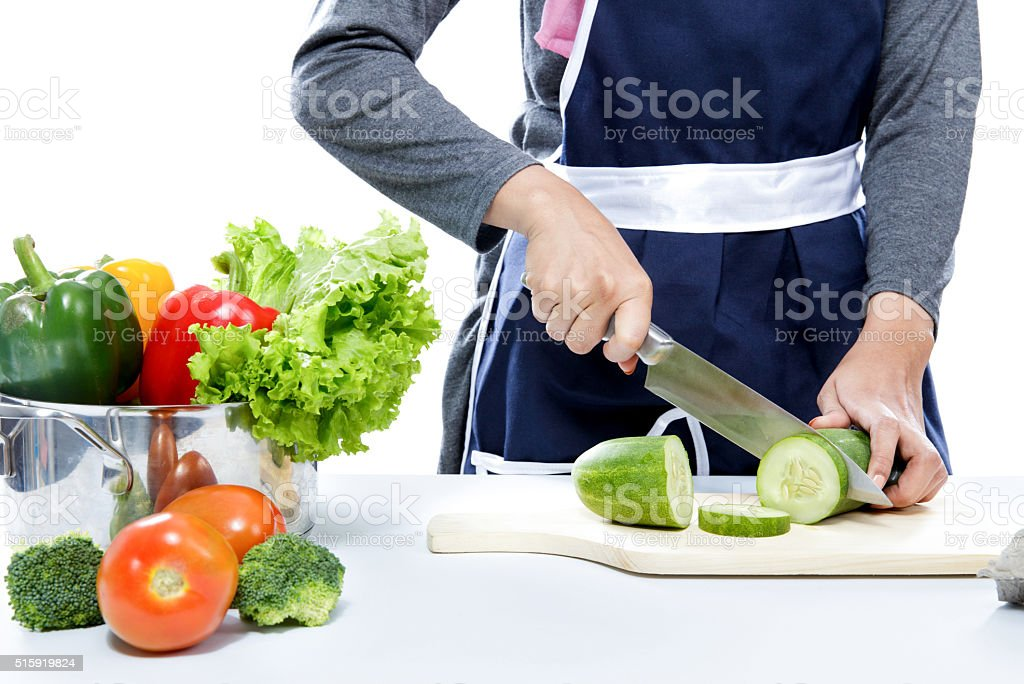 hands of housewife cutting cucumber stock photo