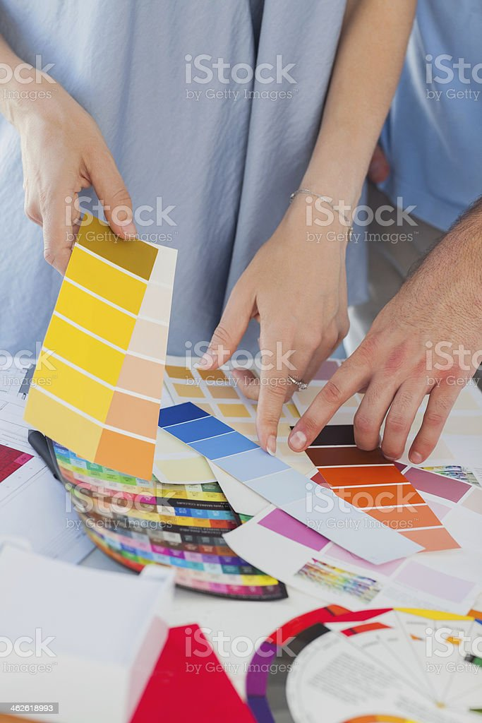 Hands of Interior designers pointing at colour charts royalty-free stock photo