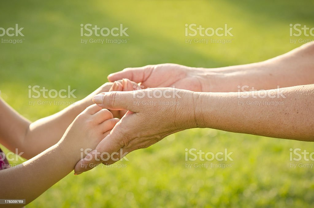 Hands of little girl and senior woman royalty-free stock photo