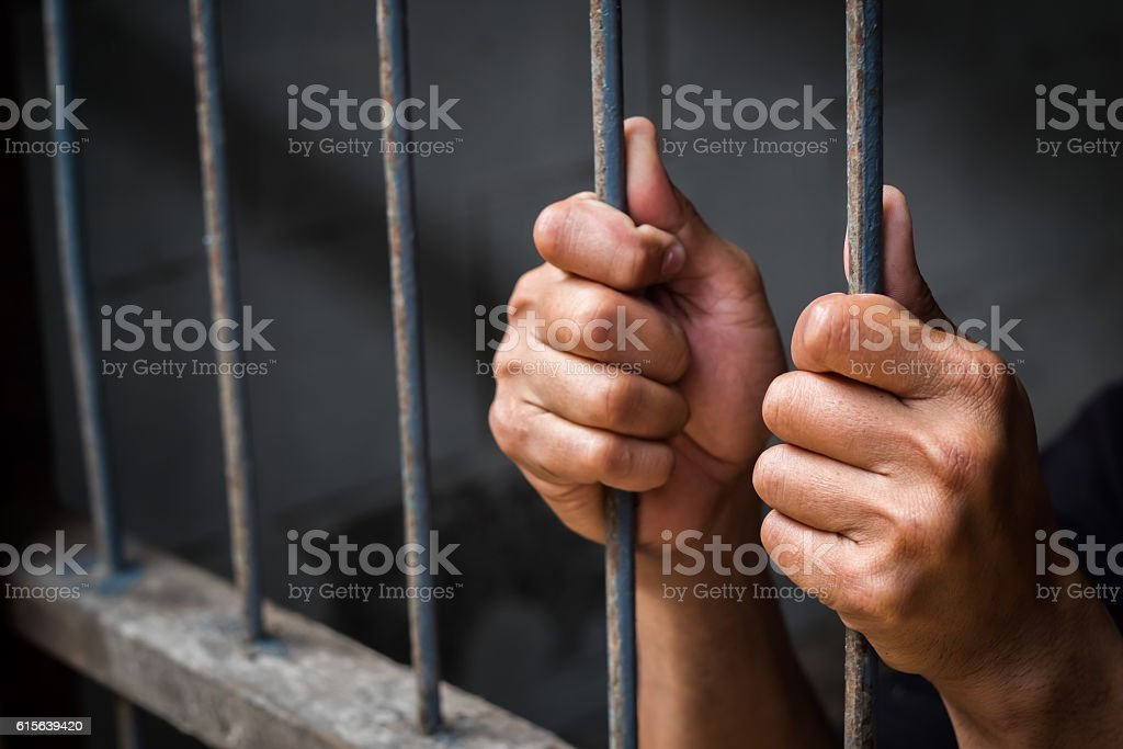 Hands of man behind jail bars. stock photo