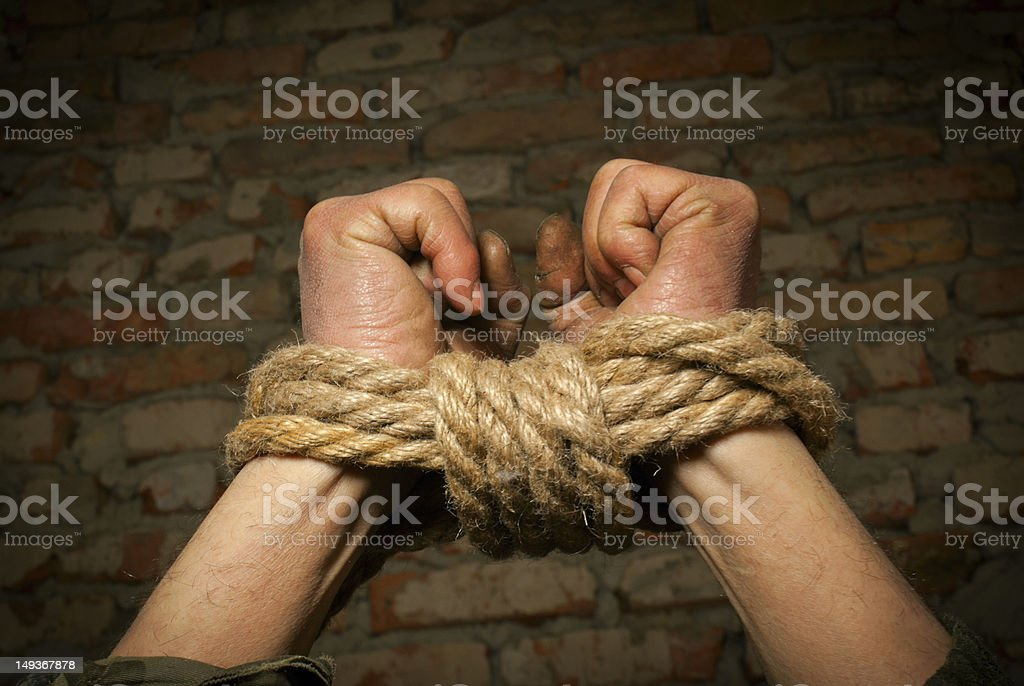 Hands of man tied up with rope royalty-free stock photo