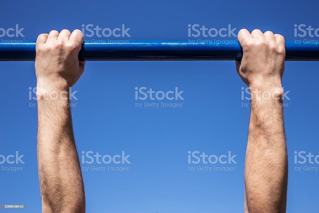 hands of man which tightened on a horizontal bar stock photo