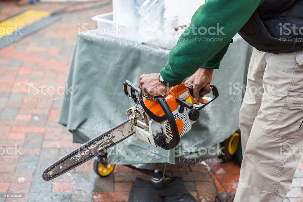 Hands of Man With Chainsaw Getting Ready For Ice Carving stock photo