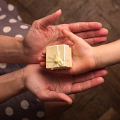Hands of mother and child receiving gifts