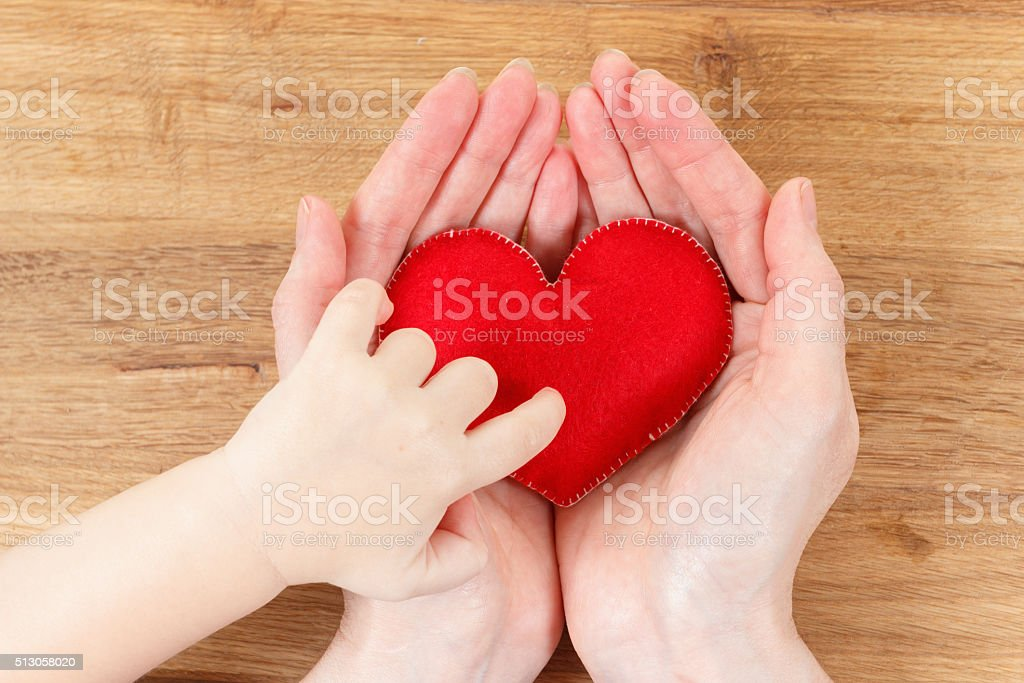Hands of mother and son holding heart symbol stock photo
