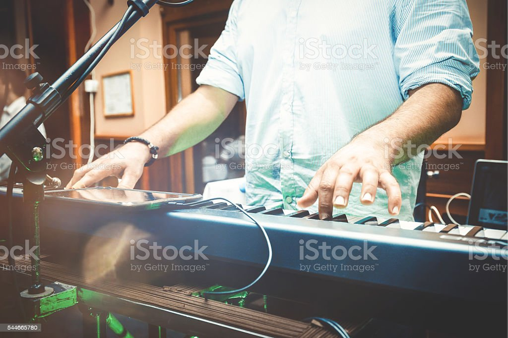 hands of musician playing keyboard in concert stock photo