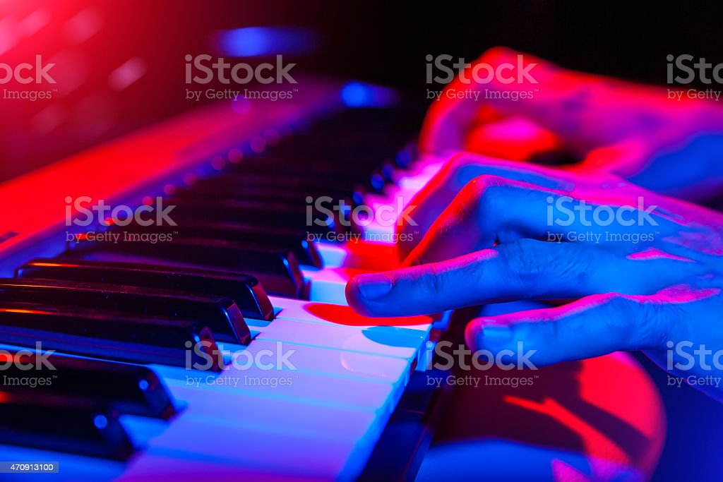 hands of musician playing keyboard in concert with shallow depth stock photo