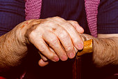 Hands of old lady with walking stick.