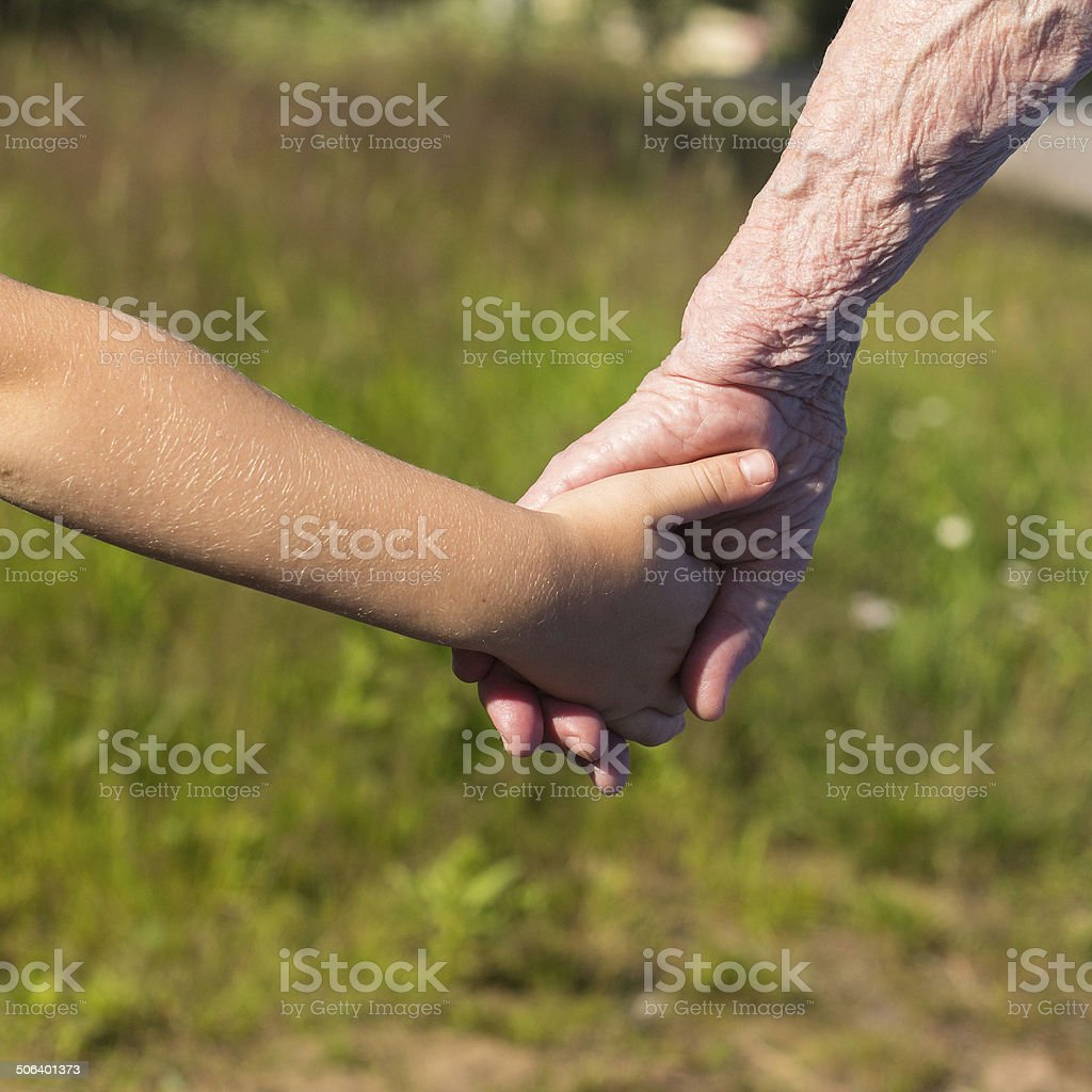 Hands of old woman and child. stock photo