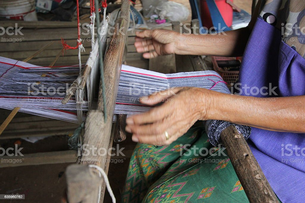 Hands of old woman who weaves on a loom, stock photo