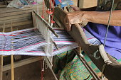 Hands of old woman who weaves on a loom,