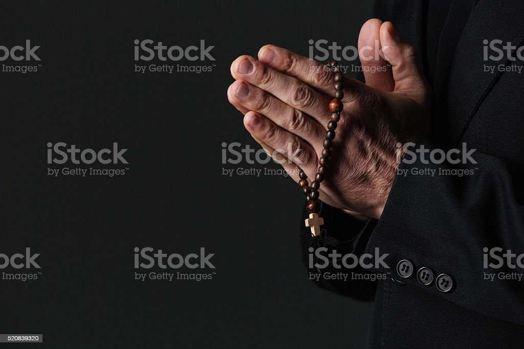 Hands of priest holding rosary and praying stock photo