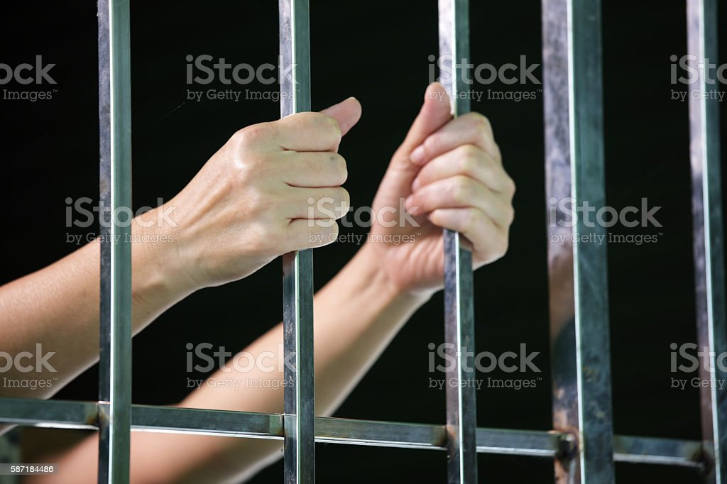 hands of prisoner in jail stock photo