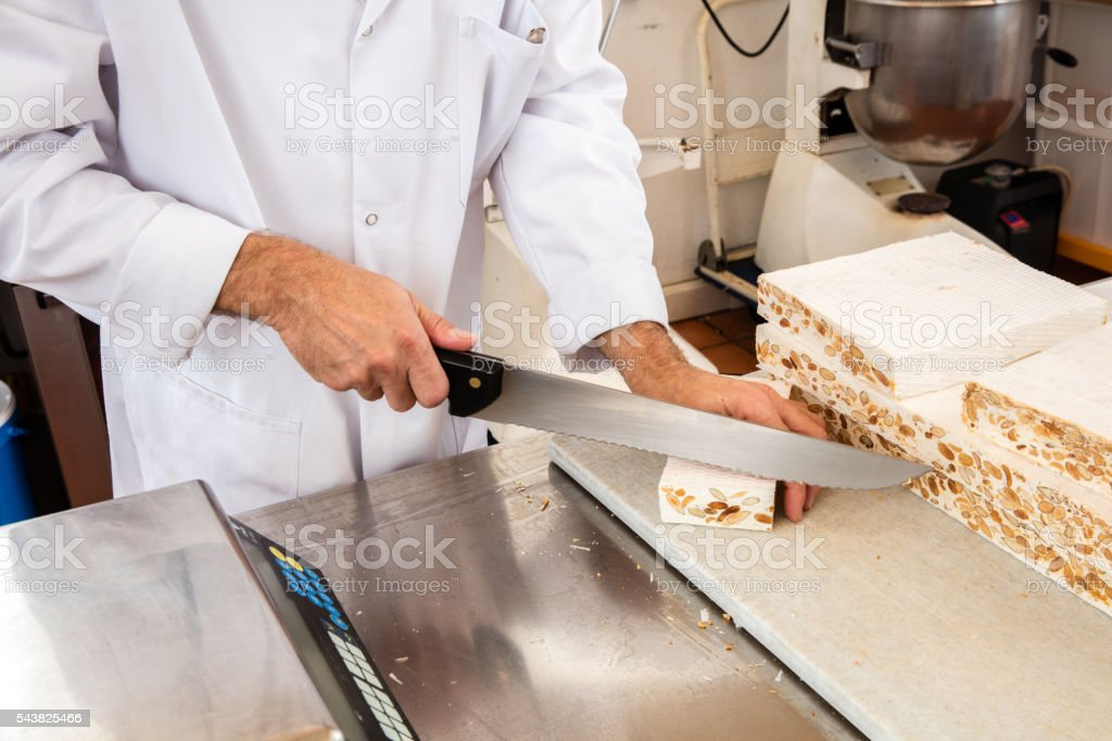 hands of professional nougat maker cutting and slicing portions stock photo