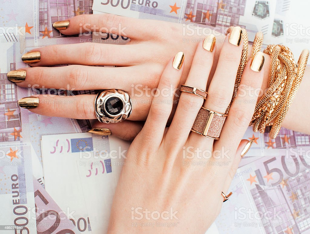 hands of rich woman with golden manicure and many jewelry stock photo
