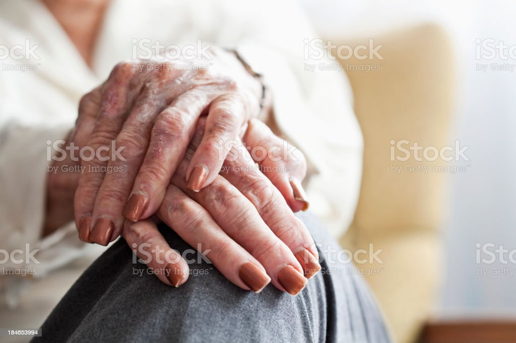 Hands of senior woman resting on her knee stock photo