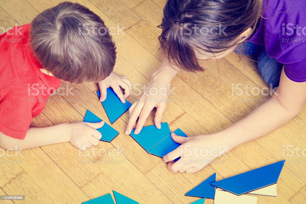 hands of teacher and child playing with geometric shapes stock photo