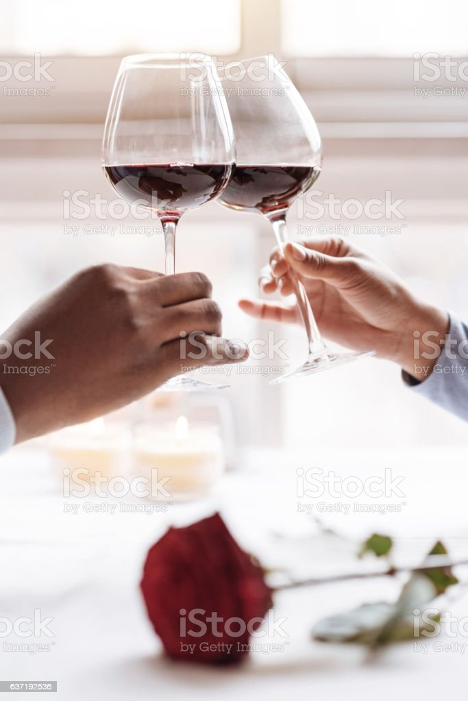 Hands of the African American couple holding wineglasses stock photo