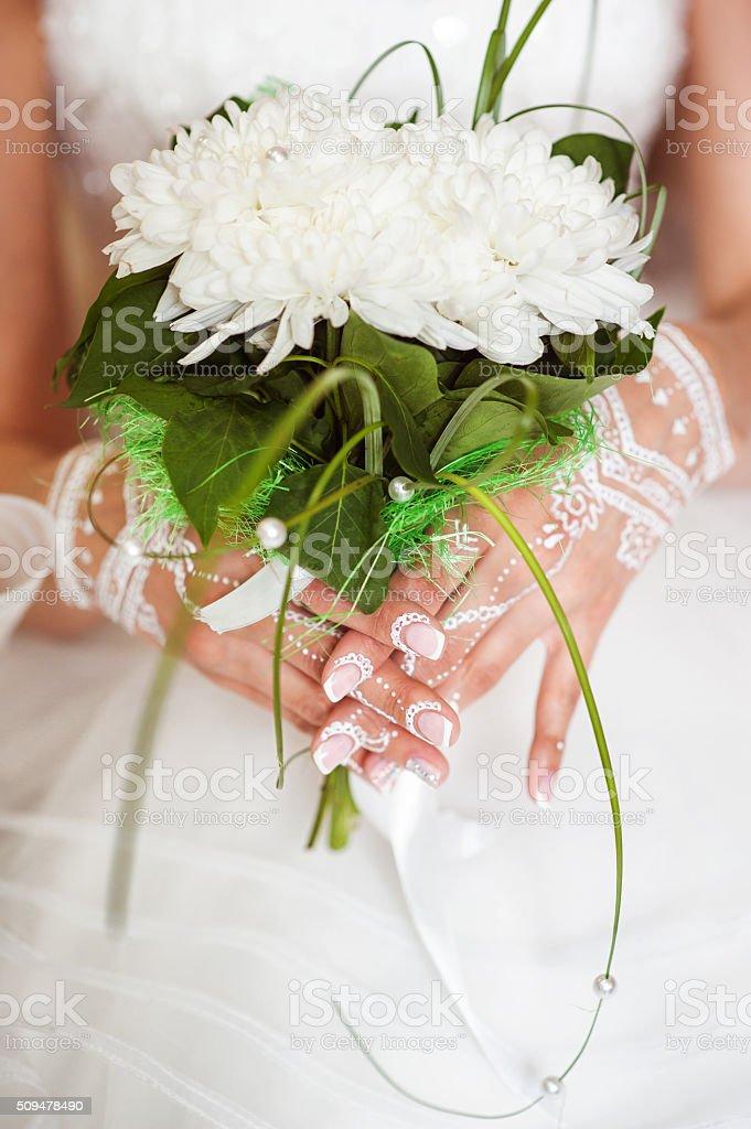 Hands of the bride. Mehendi white henna stock photo