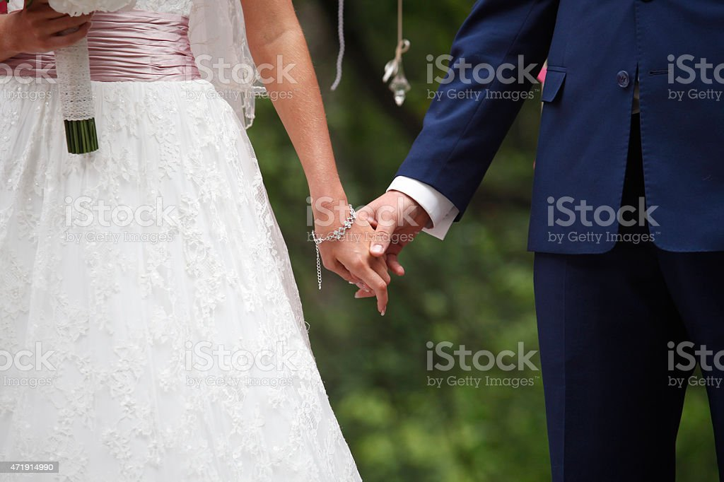 Hands of the groom and the bride stock photo