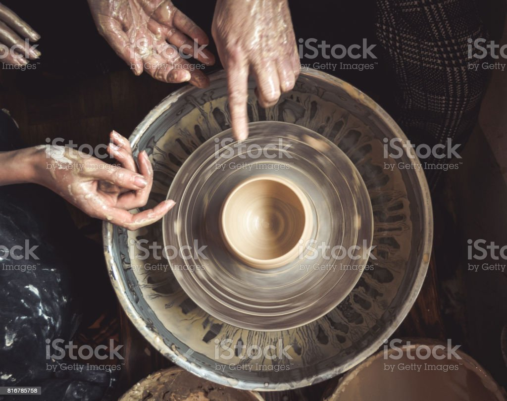Hands of the master potter and vase of clay on the potter's wheel stock photo