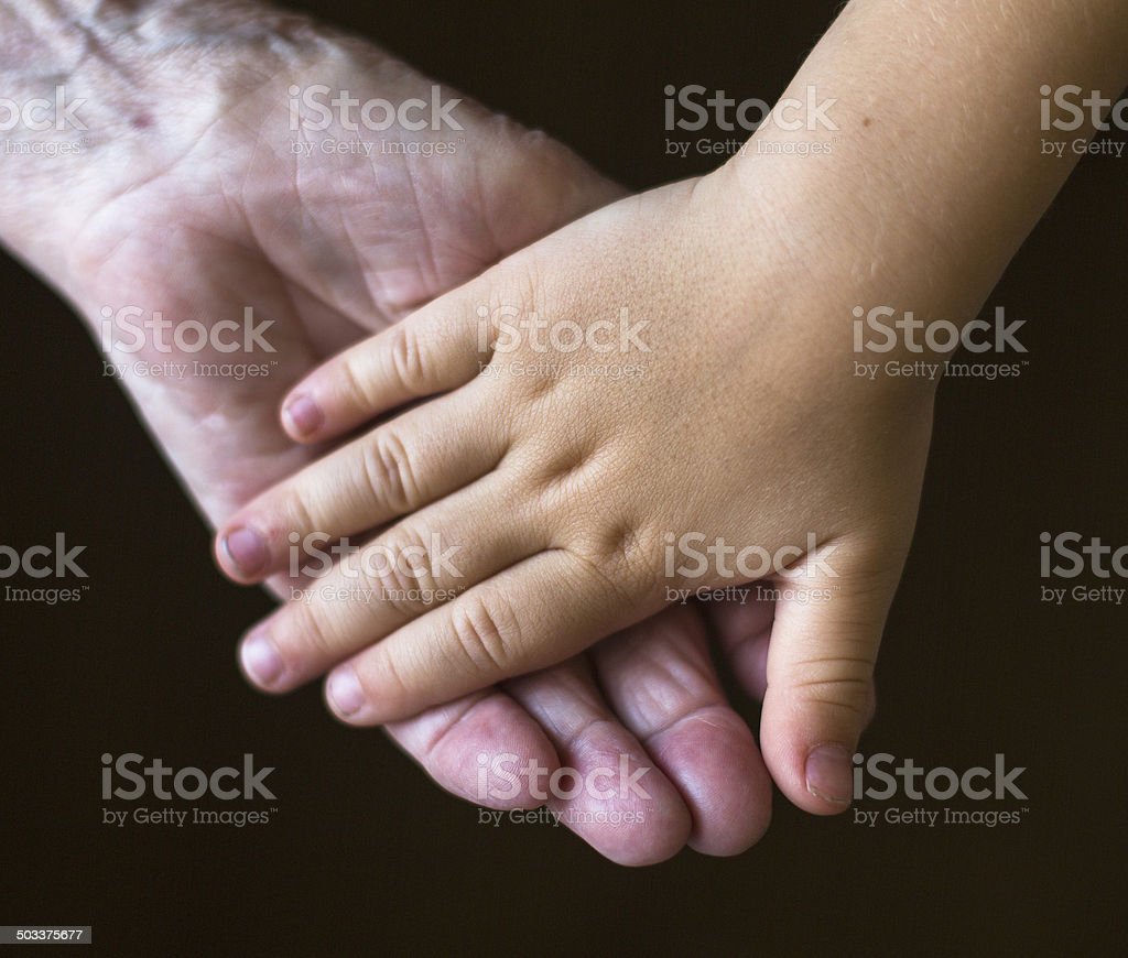 Hands of the old woman and child. stock photo