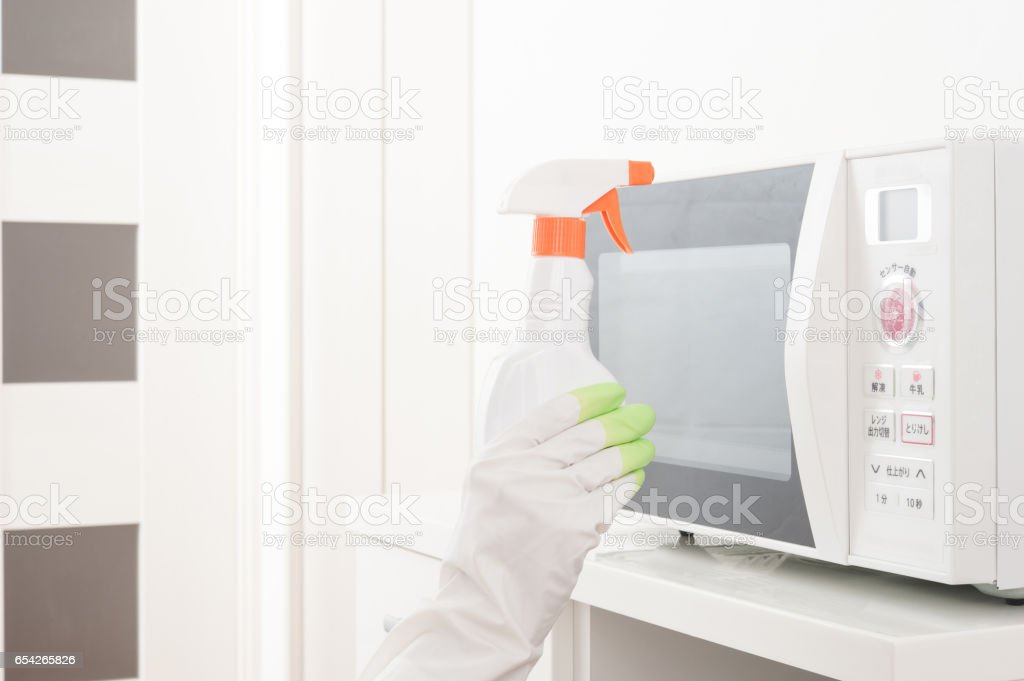 Hands of the people to clean the microwave oven stock photo