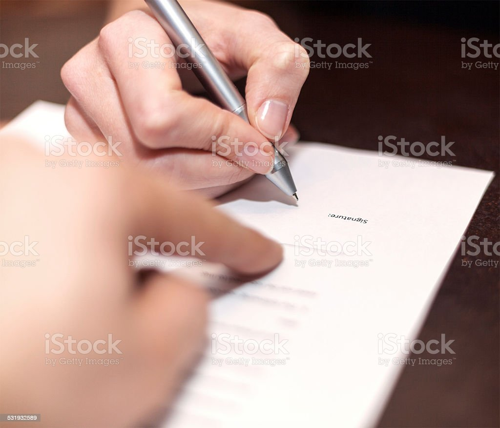 Hands of two people signed the document. stock photo