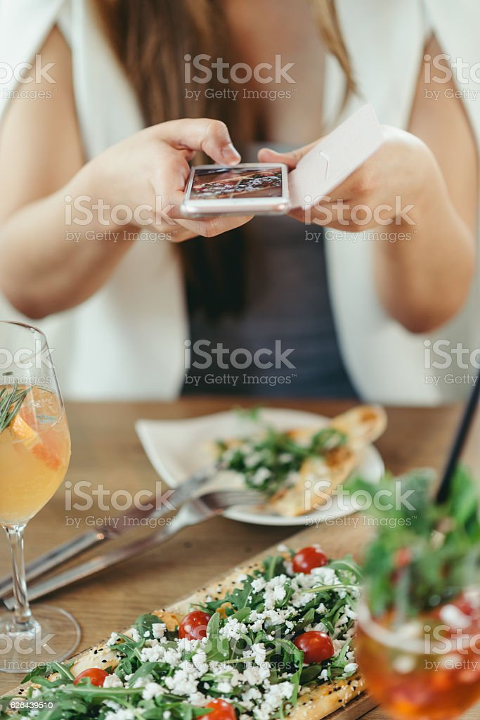Hands of unknown person making a foto from turkish pide stock photo